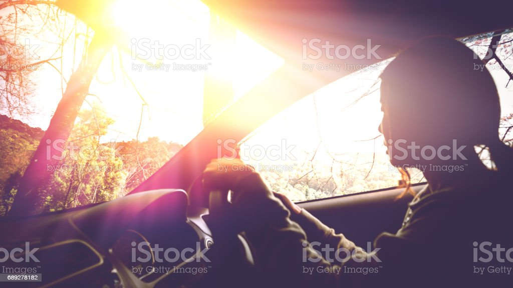 Sun during the day time driving on the road at speed. women driving car stock photo