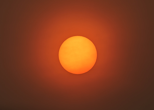 Smoke and ash particles creating eerie sun glow in San Francisco Bay Area.