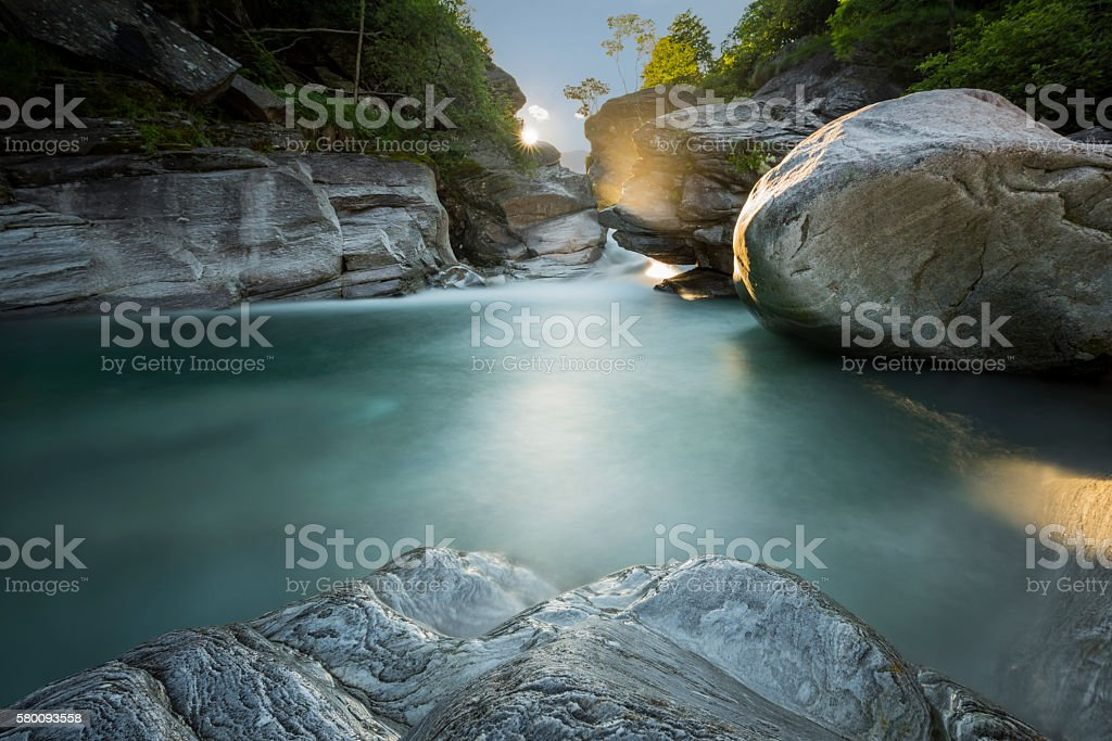 Sun filtering through rocks stock photo