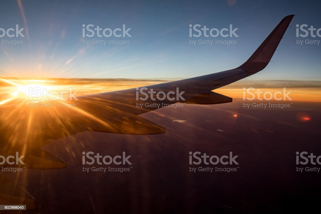 Sun flare over wing of plane flying at dusk stock photo