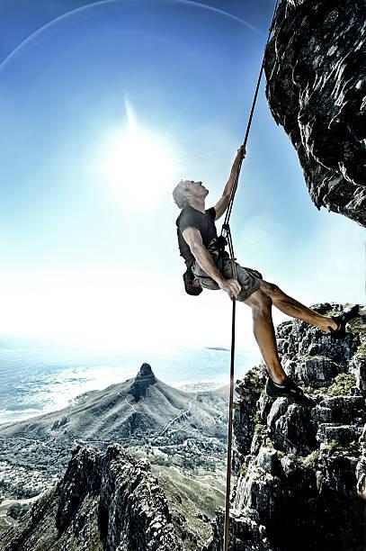 Sun flares surround abseiling climber on Table Mountain stock photo