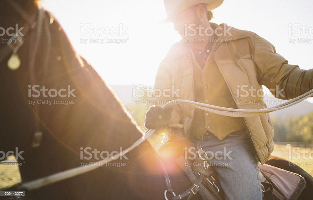 Sun glares as man holds back reins while riding horseback stock photo