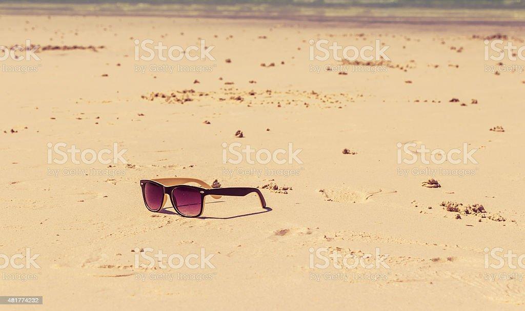 Sun glasses lie on a beach near the sea stock photo