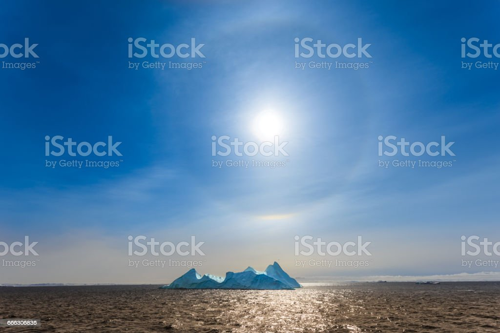 Sun Halo shining over the blue iceberg and ocean, North Greenland stock photo
