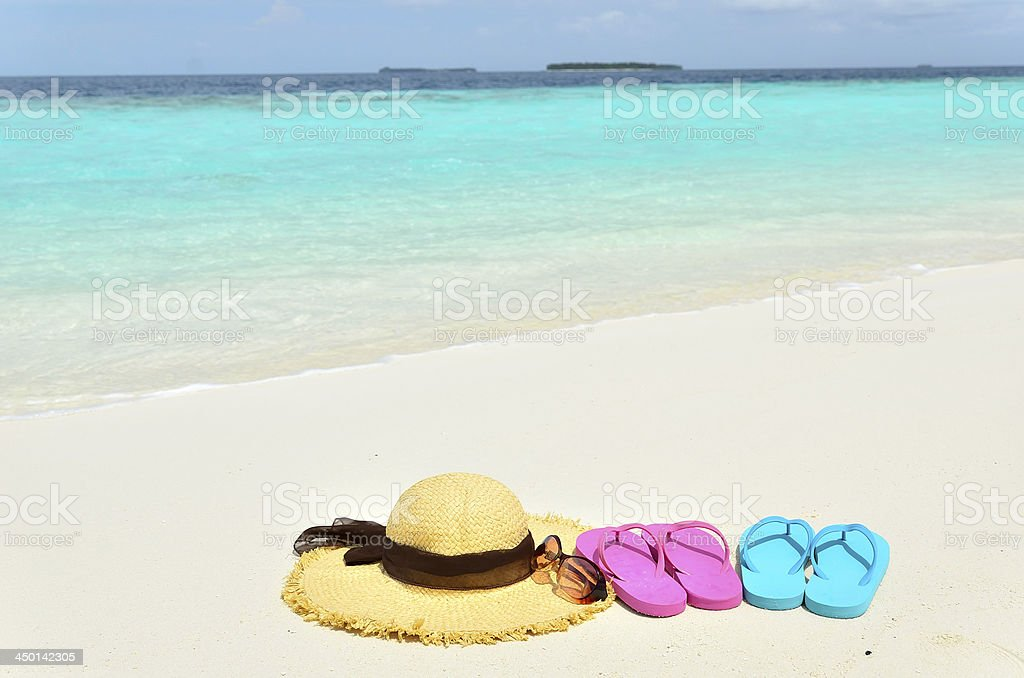 b97af4e17 Sun hat sunglasses and colored sandals on the sandy beach - Stock image .