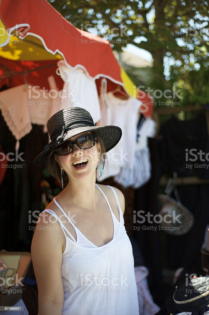 Sun hat wearing women laughing while shopping at flea market royalty-free stock photo