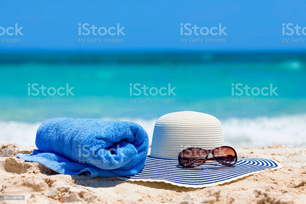 Sun hat with sunglasses and towel on beach stock photo