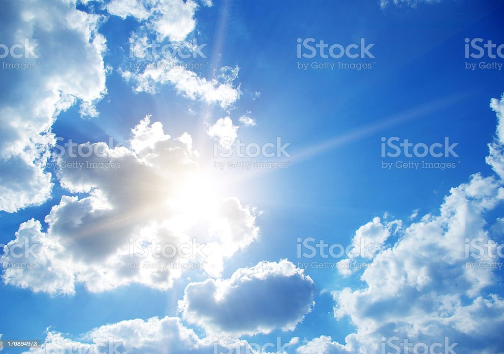 Sun hiding behind cloud formation on a clear sky royalty-free stock photo