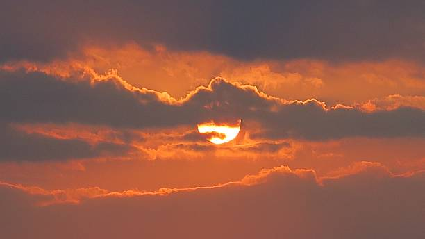 Sun hiding in clouds sunset stock photo