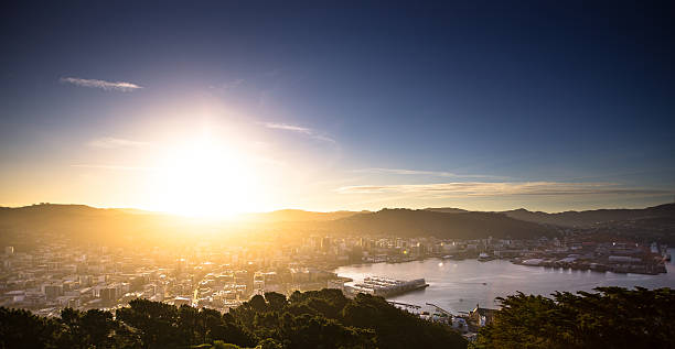 Sun Hitting the Horizon Over Wellington Harbour Vie of Wellington and its harbour as the sun begins to sink below the horizon at sunset. Seen from Mount Victoria. mt victoria canadian rockies stock pictures, royalty-free photos & images
