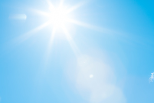 Bright sun with beautiful beams in a blue sky. Space for copy. High resolution - 50 megapixels.