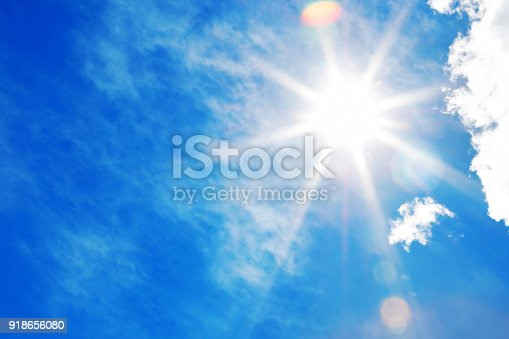 Bright sun with beautiful beams in a blue sky with light clouds. Space for copy.