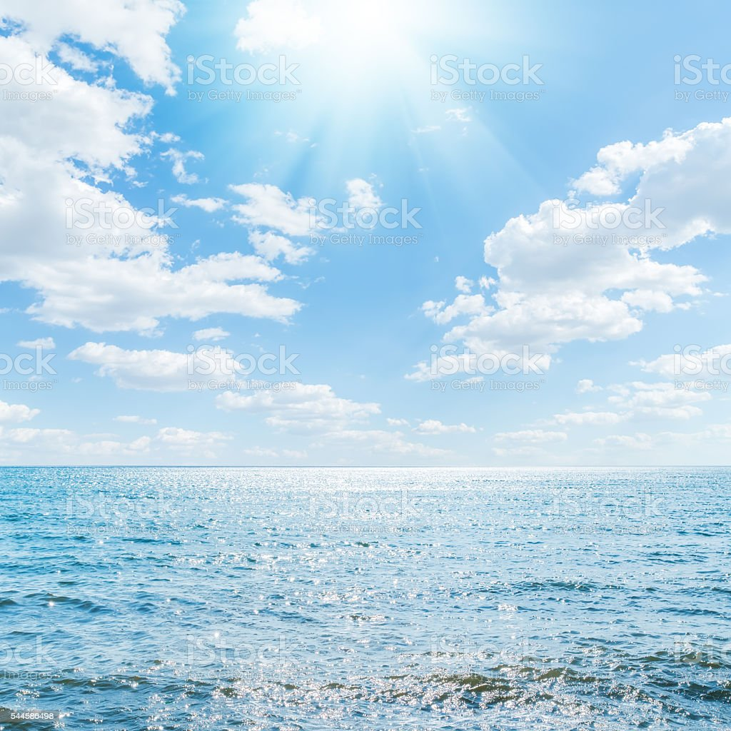 sun in clouds over blue sea stock photo