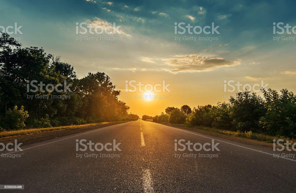 Sonne in den Horizont über Asphaltstraße - Lizenzfrei Abenddämmerung Stock-Foto