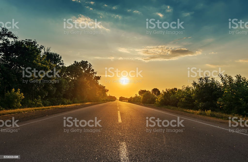 sun in horizon over asphalt road stock photo