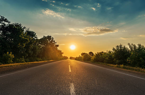 sun in horizon over asphalt road sun in horizon over asphalt road vanishing point stock pictures, royalty-free photos & images