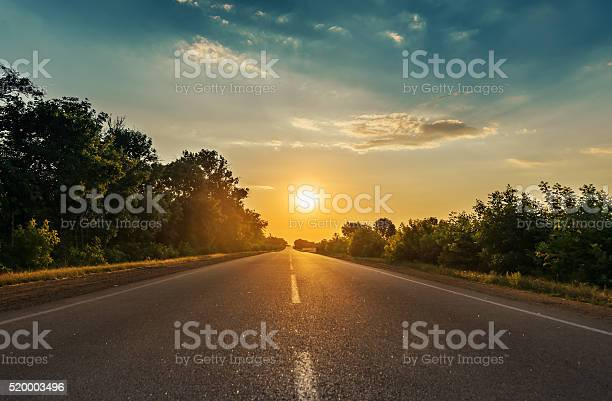 Photo of sun in horizon over asphalt road