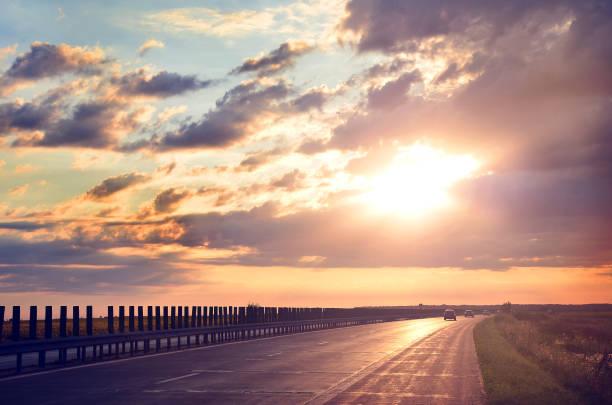 Sun in horizon over asphalt road. Way forward stock photo