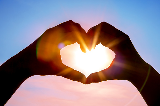 A DSLR photo of hands making a heart shape with the sun with beautiful sunbeams inside. Blue sky background. Space for copy.
