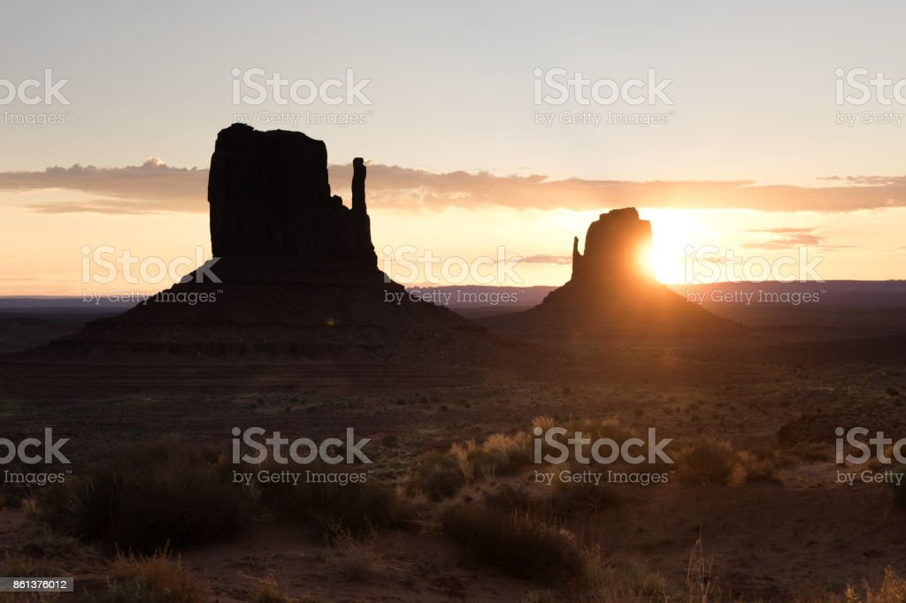 Sun is rising behind rock in Monument valley, USA stock photo