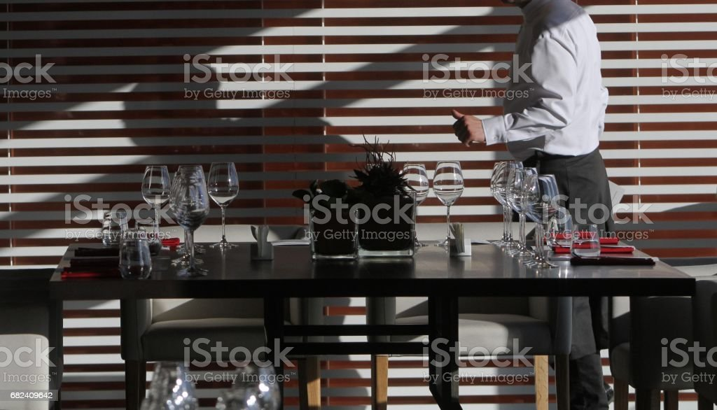 Sun light illuminates a wooden table full of empty glasses and white candles royalty-free stock photo