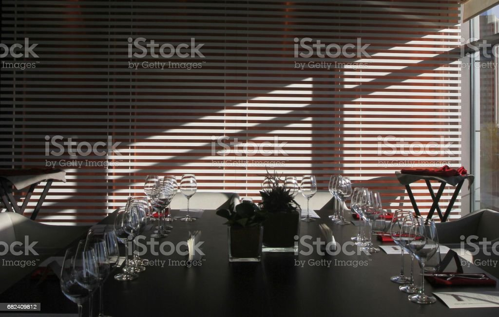 Sun light illuminates a wooden table full of empty glasses and white candles 免版稅 stock photo