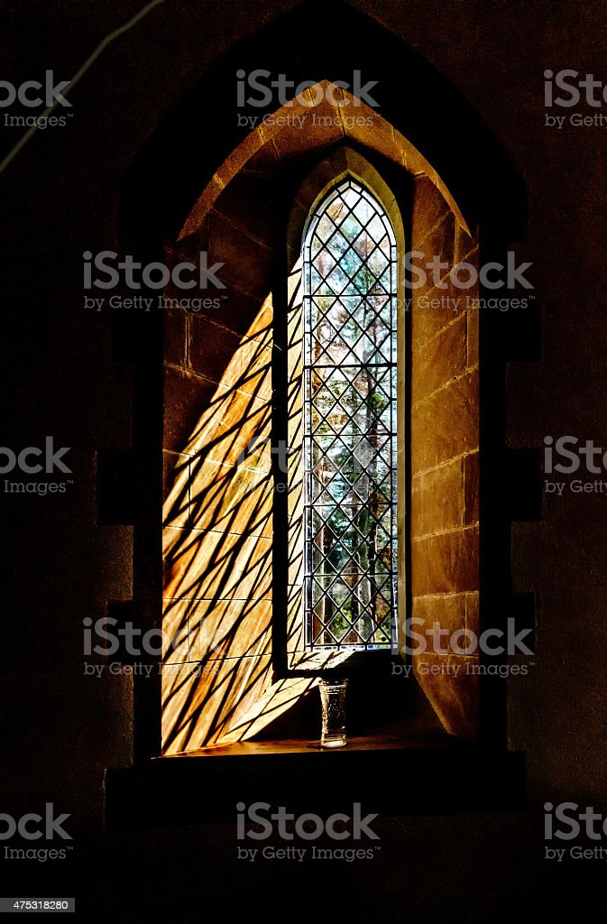 Sun lit arched leaded stain glass window with vase stock photo