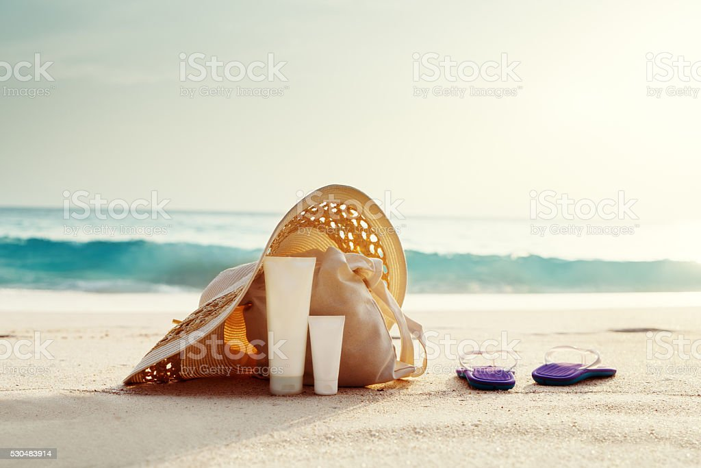 Sun lotion, hat  with bag at the tropical beach stock photo