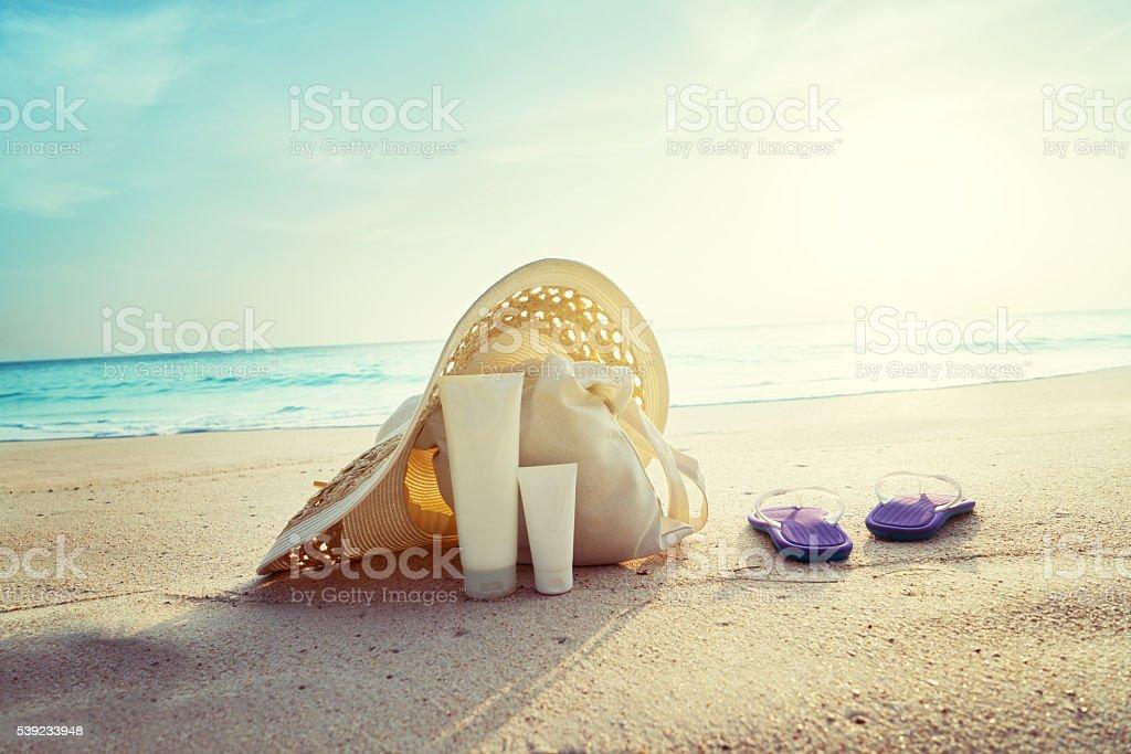 Crema de sol y sombrero con bolsa en la playa tropical foto de stock libre de derechos