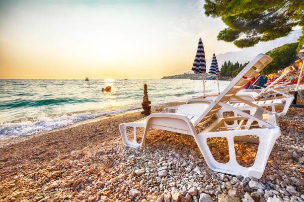 Sun loungers and beach umbrellas at sunset on the beach of Gradac in Makarska riviera. stock photo