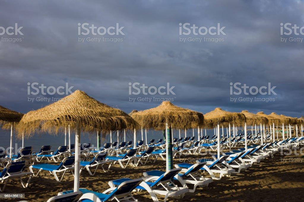 Leżaki na plaży z burzliwym niebem - Zbiór zdjęć royalty-free (Bez ludzi)