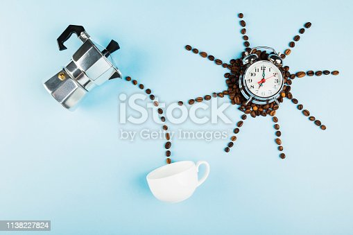 istock Sun made of coffee beans on blue background. Concept begins morning with coffee. Top view. Food background 1138227824