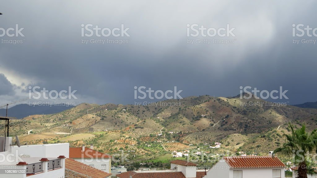 Sun not shining on hill side across rooftops in Andalusian village