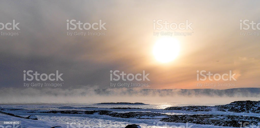 Sun over cold Foggy land covered with Snow stock photo