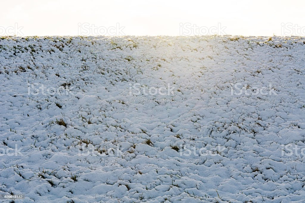 Sun over melting snow on th grass slope stock photo