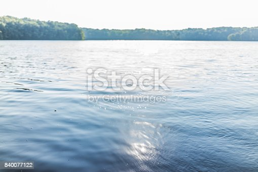 istock Sun path reflection over lake in summer on bright day with waves and flare 840077122