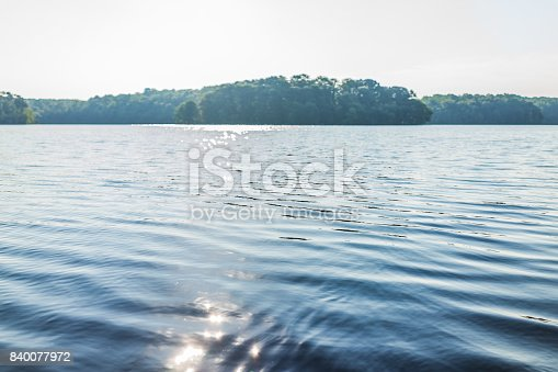 istock Sun path reflection over lake in summer on bright day with waves and flare 840077972