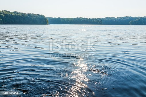 istock Sun path reflection over lake in summer on bright day with waves and flare 840078454