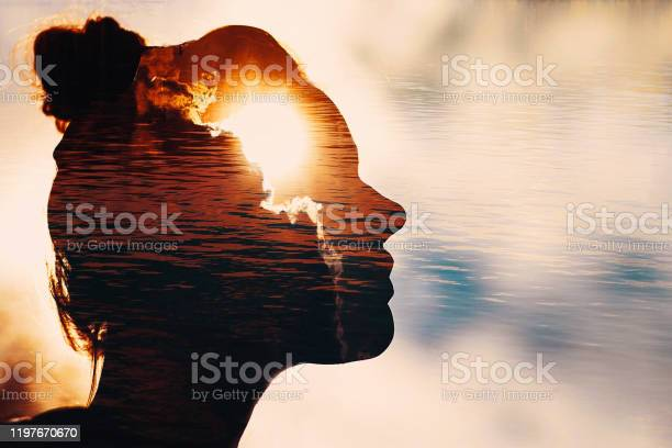 Photo of Sun peeks out from behind the clouds in woman's head
