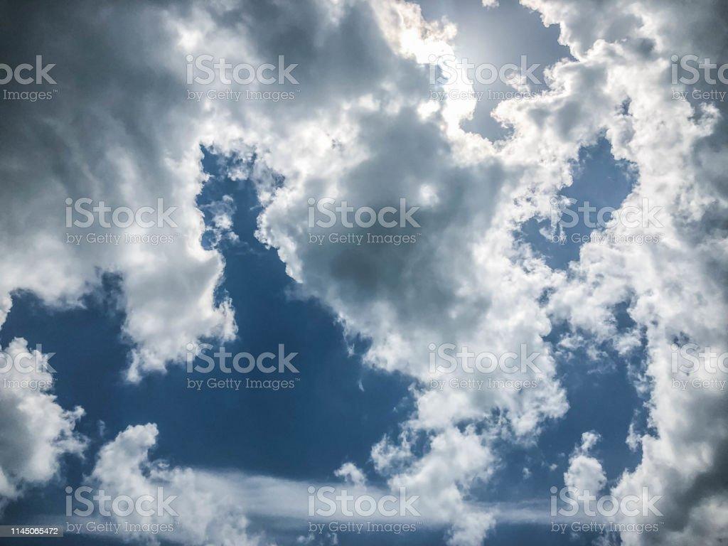 Sun peeks through clouds with sunbeam