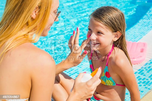 Mother applying suntan lotion to her daughter and having great time together at swimming pool