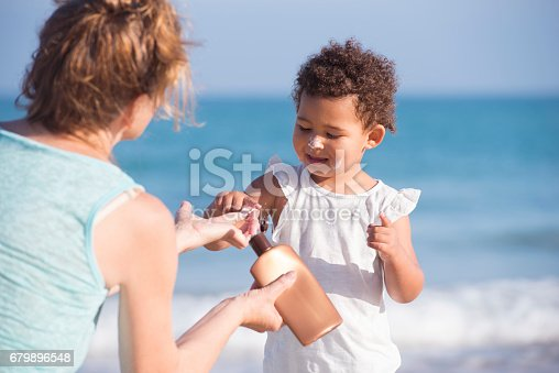 2 years old little girl using sun protection cream for skin care. Grandmother showing little girl how to apply sunscreen. Grandmother and daughter enjoying summer holiday on sea beach together.