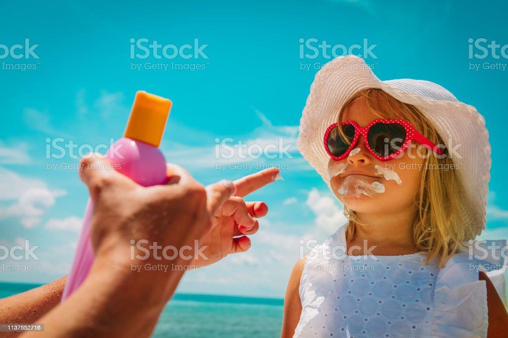 sun protection - mom put suncream on little girl face at beach stock photo