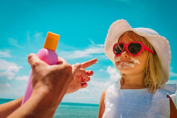 Sonnenschutz-Mama legt Sonnencreme auf das Gesicht des kleinen Mädchens am Strand – Foto