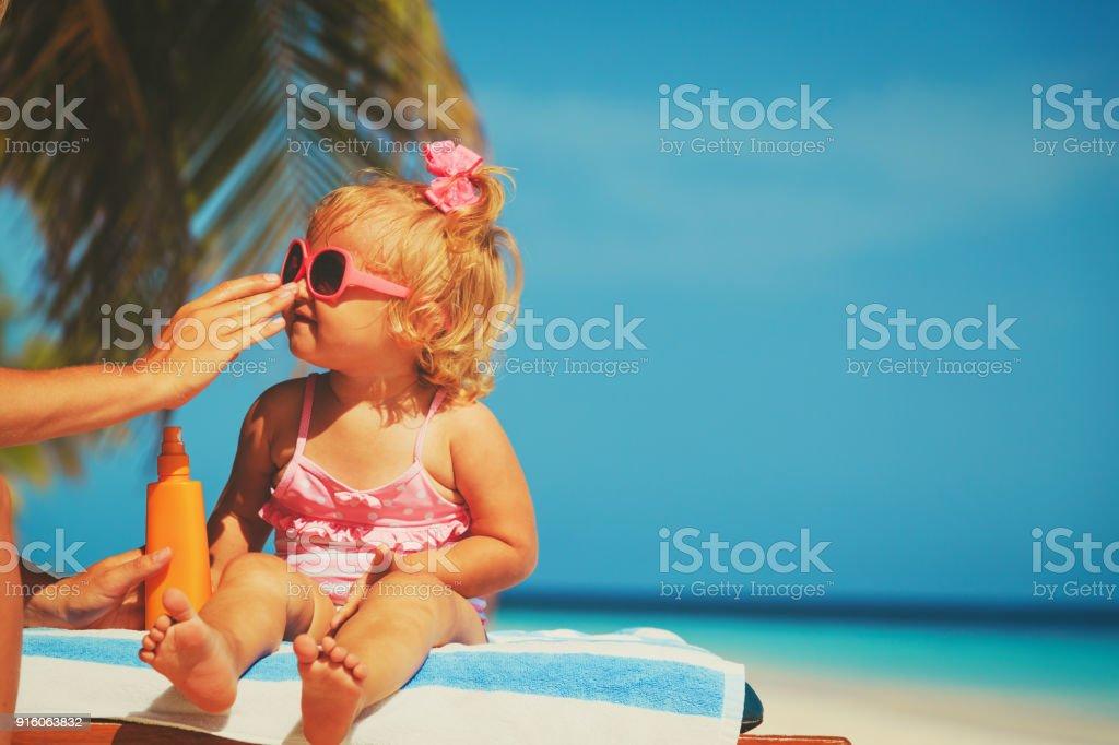 ビーチ - 母娘の顔に日焼け止めクリームを適用することで日焼け防止 ストックフォト
