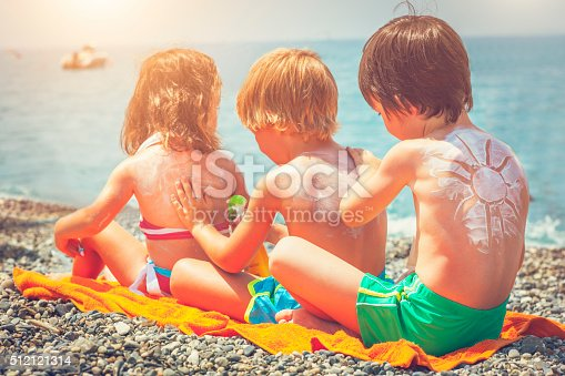 Little boys and girl applying sun protection lotion on the beach