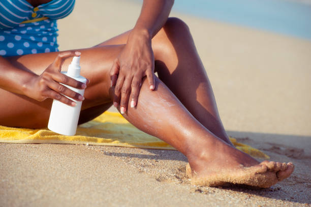 Sun protection spray to keep your skin healthy. Close up unrecognized woman applying, spraying sun protection cream on her legs. suntan lotion stock pictures, royalty-free photos & images