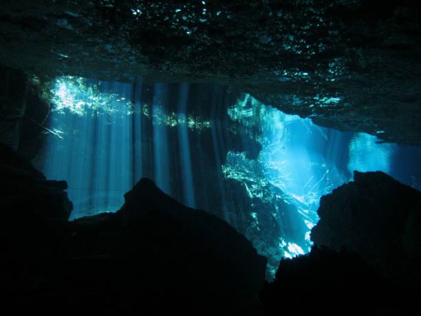 solens strålar in i vattnet i en undervattens grotta. - penetrating bildbanksfoton och bilder