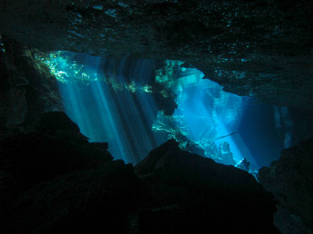 Sun rays entering the water in an underwater cave. stock photo