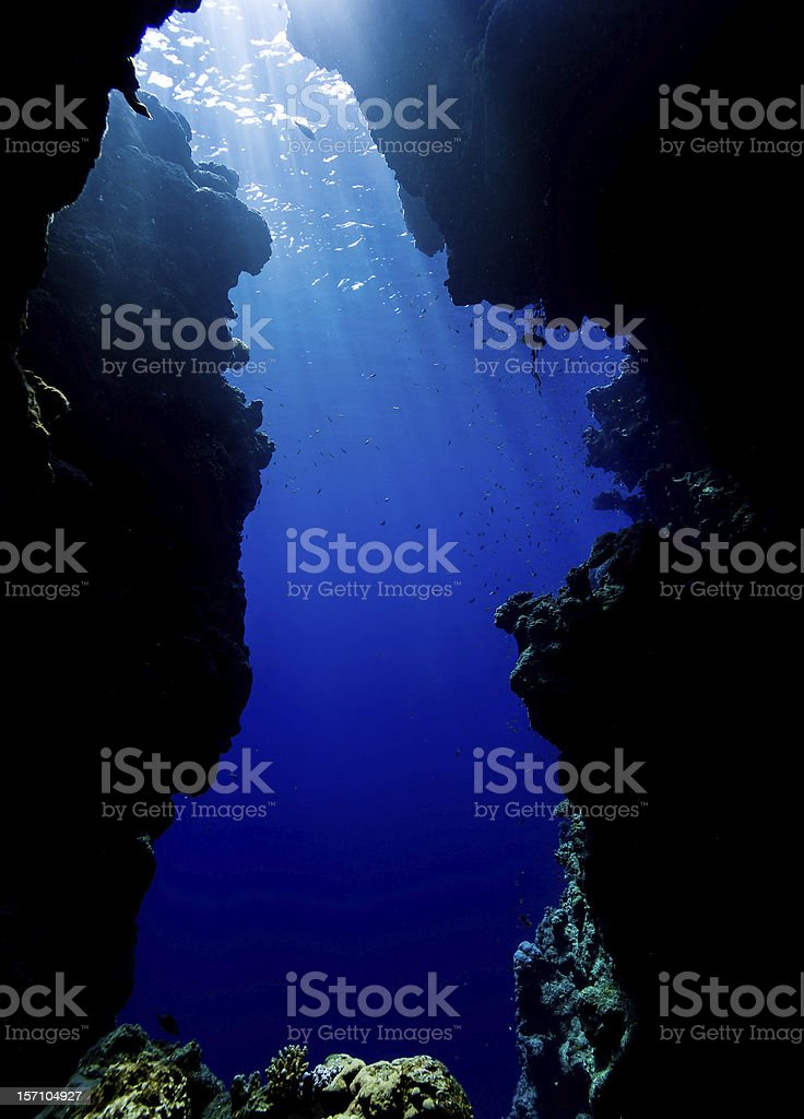 Sun rays filter down through an underwater cave exit stock photo